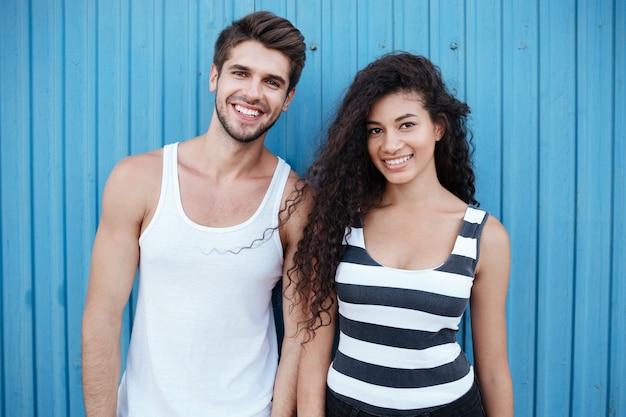 Retrato de um jovem casal alegre em pé junto à parede azul