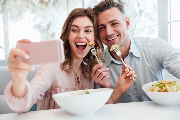 Retrato de um jovem casal alegre tomando uma selfie