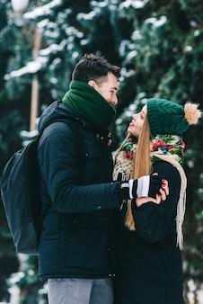 Retrato de um jovem casal amoroso feliz, unindo-se com ternura. eles estão olhando um para o outro e sorrindo enquanto ficam ao ar livre no inverno