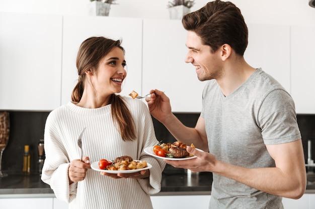 Retrato de um jovem casal amoroso segurando pratos