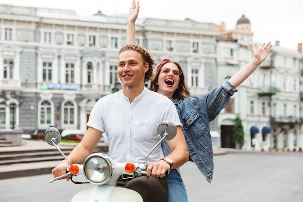 Retrato de um jovem casal animado, andando juntos em uma moto na rua da cidade