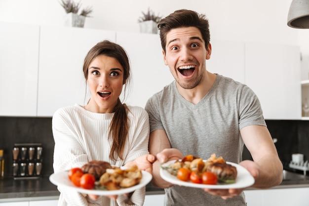 Retrato de um jovem casal animado segurando pratos