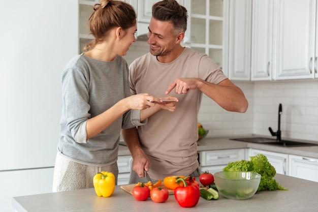Retrato de um jovem casal apaixonado, cozinhar salada juntos