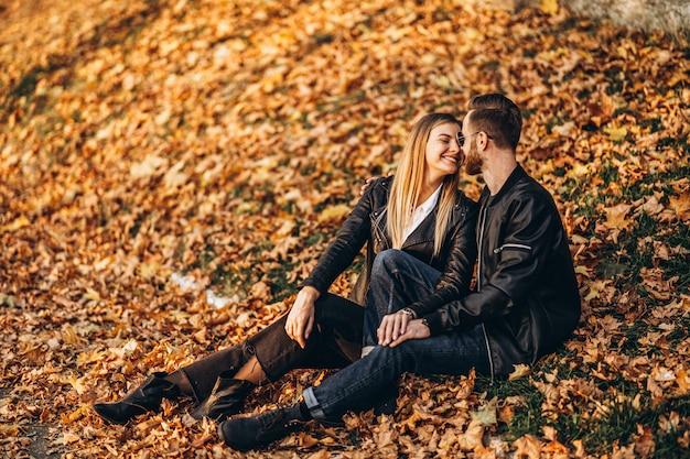 Retrato de um jovem casal apaixonado, sentado na folha de outono e curtindo a natureza