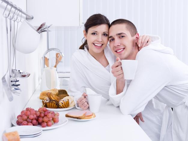 Retrato de um jovem casal apaixonado tomando café da manhã juntos