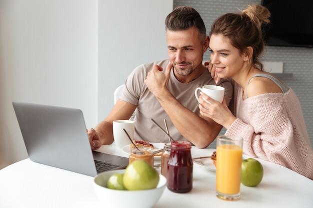 Retrato de um jovem casal apaixonado tomando café da manhã