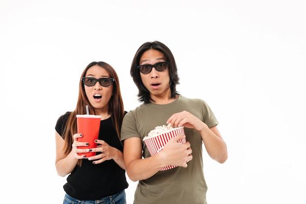 Retrato de um jovem casal asiático chocado em óculos 3d