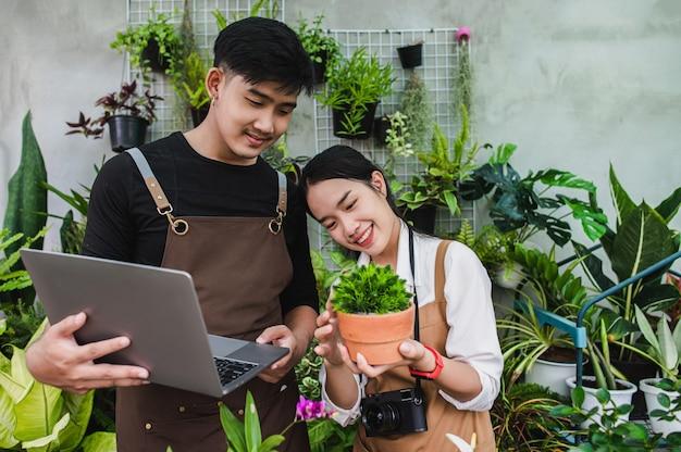 Retrato de um jovem casal asiático de jardineiros vestindo avental e usando equipamento de jardim e um laptop para pesquisar e cuidar das plantas da casa na estufa