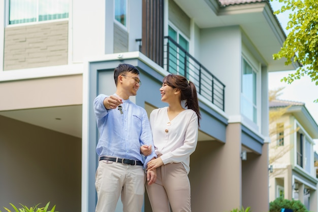 Retrato de um jovem casal asiático em pé e se abraçando e segurando a chave da casa, olhando feliz na frente de sua nova casa para começar uma nova vida. conceito de família, idade, casa, imóveis e pessoas.