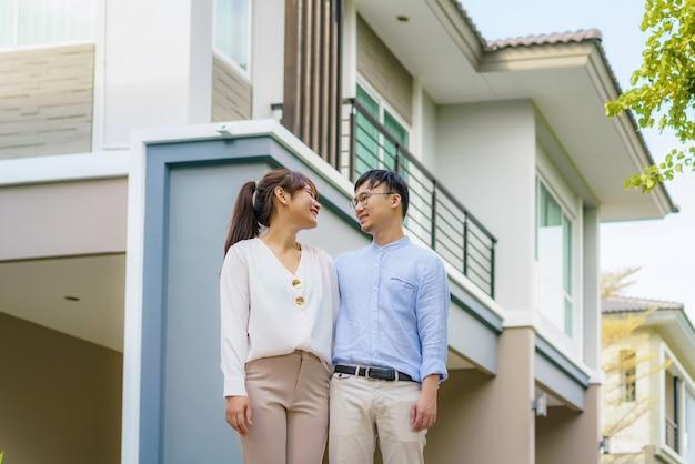 Retrato de um jovem casal asiático em pé e se abraçando, parecendo feliz na frente de sua nova casa para começar uma nova vida. conceito de família, idade, casa, imóveis e pessoas.