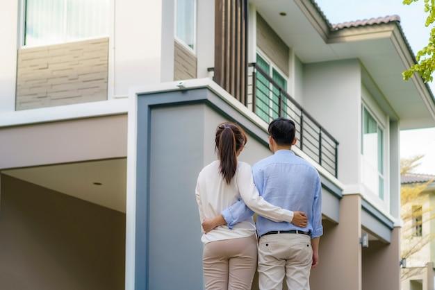 Retrato de um jovem casal asiático em pé e se abraçando, parecendo feliz na frente de sua nova casa para começar uma nova vida.
