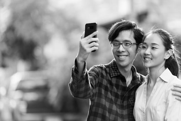 Retrato de um jovem casal asiático na rua ao ar livre em preto e branco