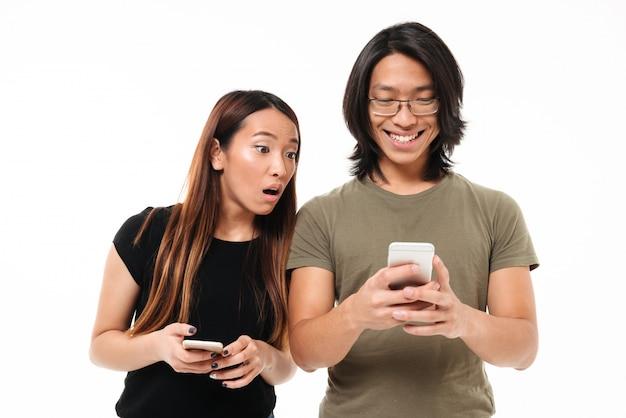 Retrato de um jovem casal asiático usando telefones móveis