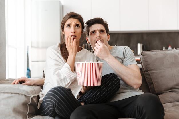 Retrato de um jovem casal assustado relaxando em um sofá