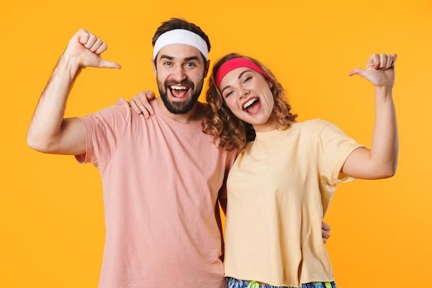 Retrato de um jovem casal atlético usando bandanas, sorrindo e apontando o dedo para si mesmo, isolado sobre a parede amarela
