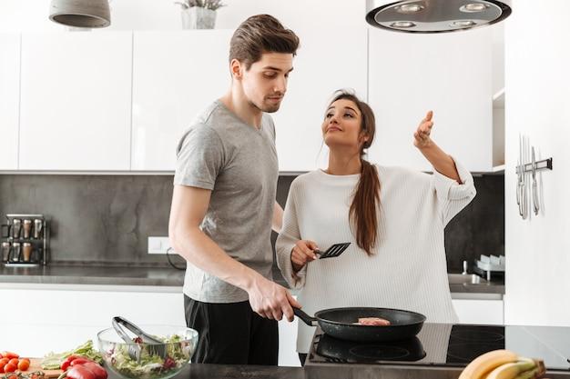 Retrato de um jovem casal atraente, cozinhando juntos
