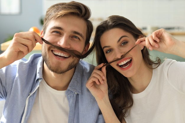 Retrato de um jovem casal brincalhão brincando com bigode falso, sentado no sofá.