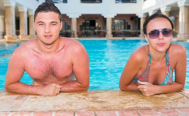 Retrato de um jovem casal bronzeado relaxando em uma piscina com colunas em estilo antigo no hotel
