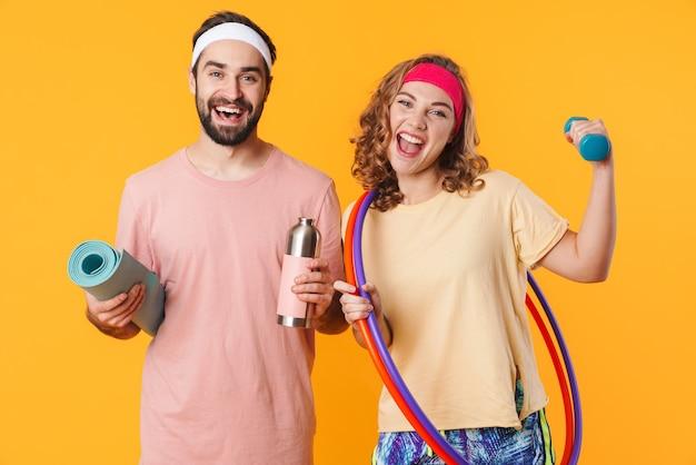 Retrato de um jovem casal caucasiano feliz fitness usando tiaras, sorrindo e segurando equipamentos esportivos isolados