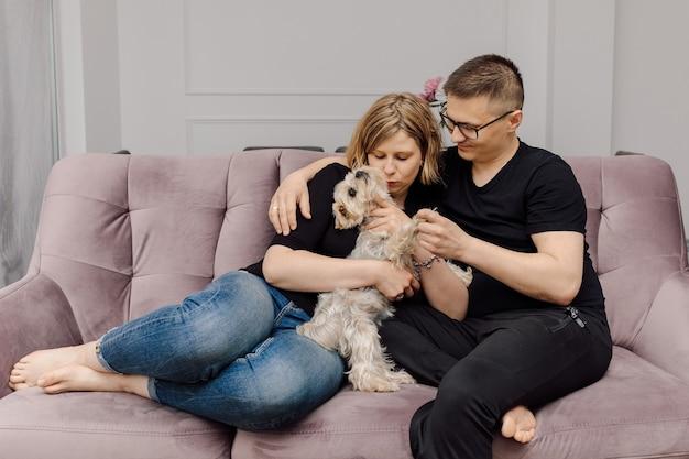 Retrato de um jovem casal com cachorro yorkshire terrier exala amor e ternura.