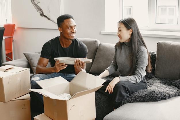 Retrato de um jovem casal com caixas de papelão na nova casa, conceito de casa em movimento.