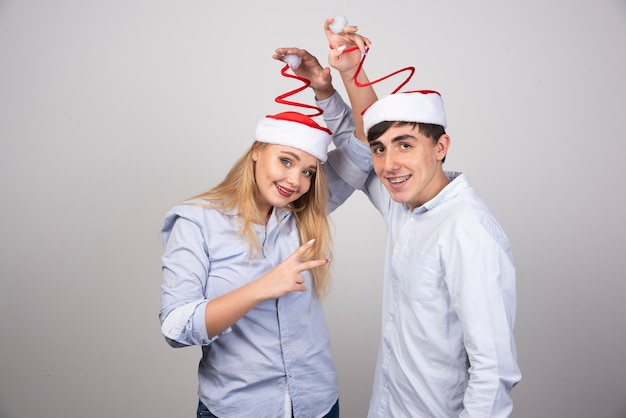 Retrato de um jovem casal com chapéu de papai noel sendo brincalhão na parede cinza.