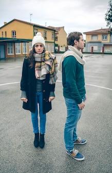 Retrato de um jovem casal com roupas de inverno, em pé ao ar livre em um dia frio e chuvoso