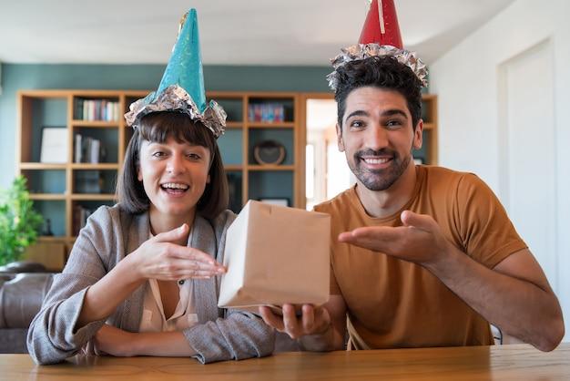 Retrato de um jovem casal comemorando o aniversário em uma chamada de vídeo com caixa de presente de casa.