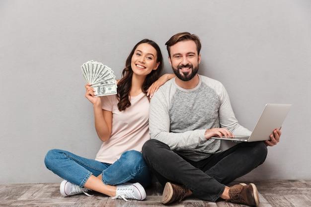 Retrato de um jovem casal confiante com computador portátil