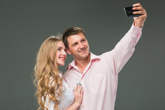 Retrato de um jovem casal dançando contra fundo cinza