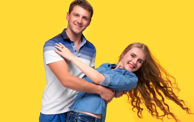 Retrato de um jovem casal dançando contra parede amarela