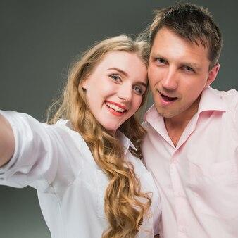 Retrato de um jovem casal dançando contra parede cinza