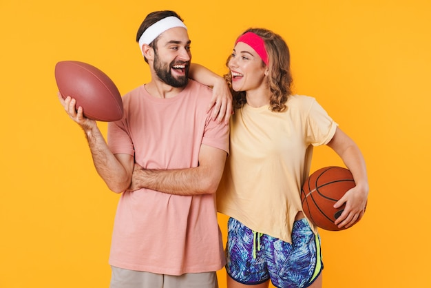Retrato de um jovem casal de fitness caucasiano feliz usando tiaras, segurando bolas esportivas isoladas