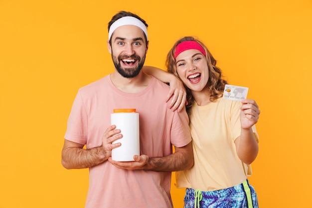 Retrato de um jovem casal de fitness caucasiano feliz usando tiaras, segurando o frasco de proteínas e o cartão de crédito isolado