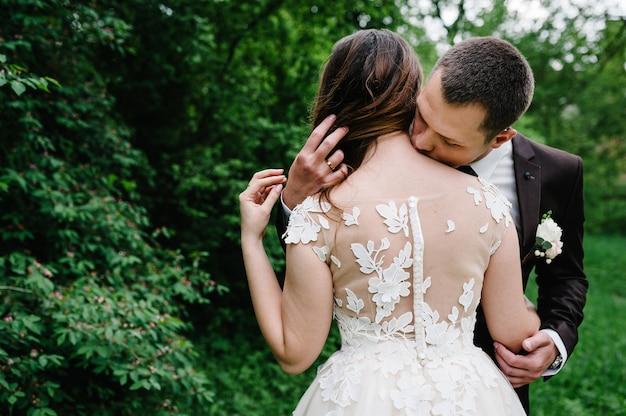 Retrato de um jovem casal de noivos beijando na natureza. recém-casados.