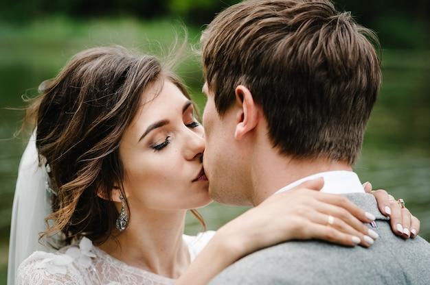 Retrato de um jovem casal de noivos beijando na natureza.