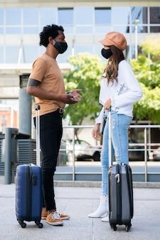 Retrato de um jovem casal de turistas usando máscara protetora e carregando uma mala enquanto está do lado de fora do aeroporto ou da estação ferroviária