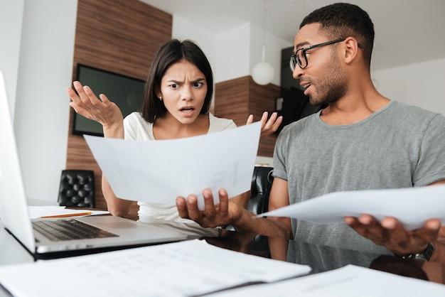 Retrato de um jovem casal discutindo sobre contas domésticas em casa enquanto olha para documentos.
