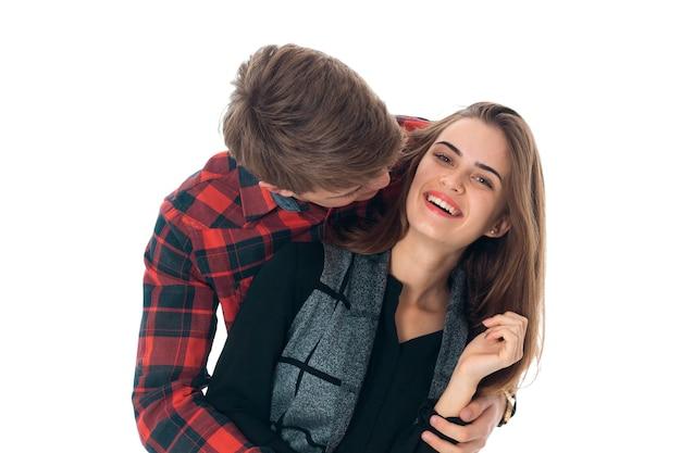Retrato de um jovem casal elegante e engraçado apaixonado se divertindo em um estúdio isolado no fundo branco