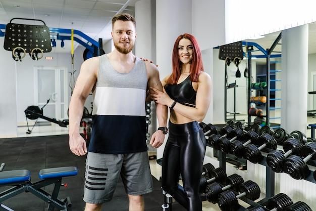 Retrato de um jovem casal em forma de pé no estúdio de fitness