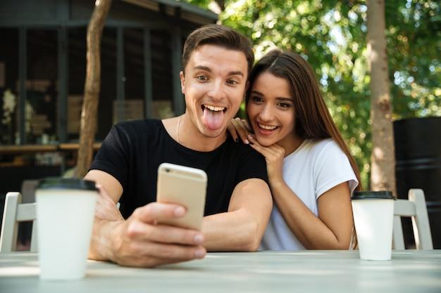 Retrato de um jovem casal engraçado, tendo selfie