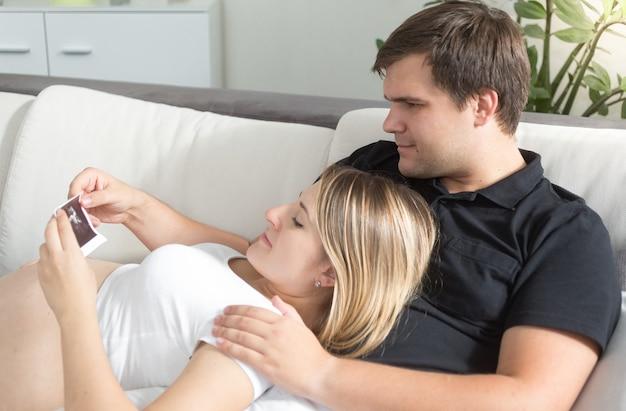 Retrato de um jovem casal esperando o bebê olhando para a ultrassonografia do feto