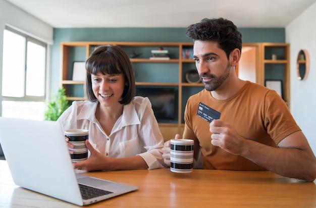 Retrato de um jovem casal fazendo compras online com um cartão de crédito e um laptop em casa.