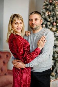 Retrato de um jovem casal feliz abraçando, acariciando, celebrando as férias de inverno juntos perto de uma árvore de natal decorada na sala de estar.