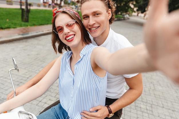 Retrato de um jovem casal feliz andando juntos em uma moto na rua da cidade, tirando uma selfie