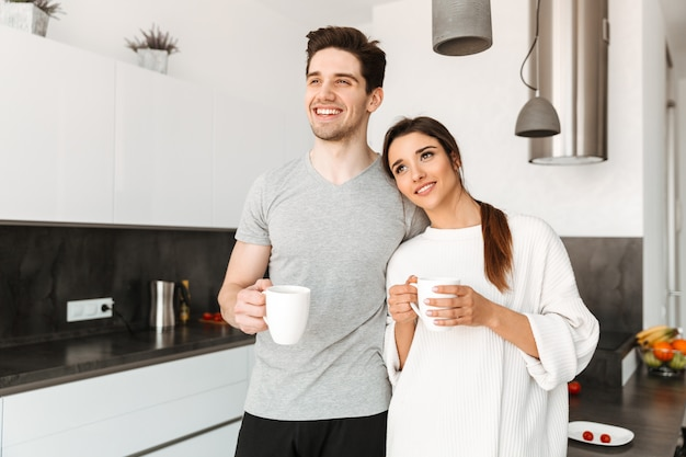 Retrato de um jovem casal feliz, bebendo café