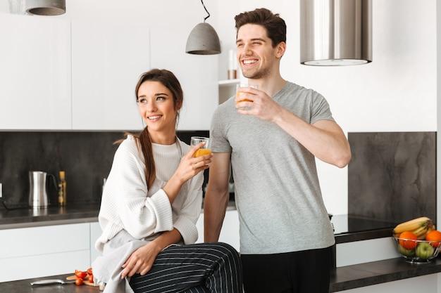 Retrato de um jovem casal feliz, bebendo suco de laranja