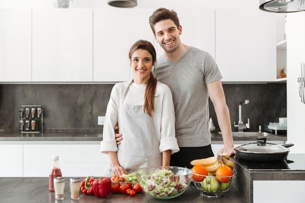 Retrato de um jovem casal feliz, cozinhando juntos