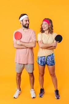 Retrato de um jovem casal feliz e esportivo usando bandanas, sorrindo e segurando raquetes de pingue-pongue isoladas