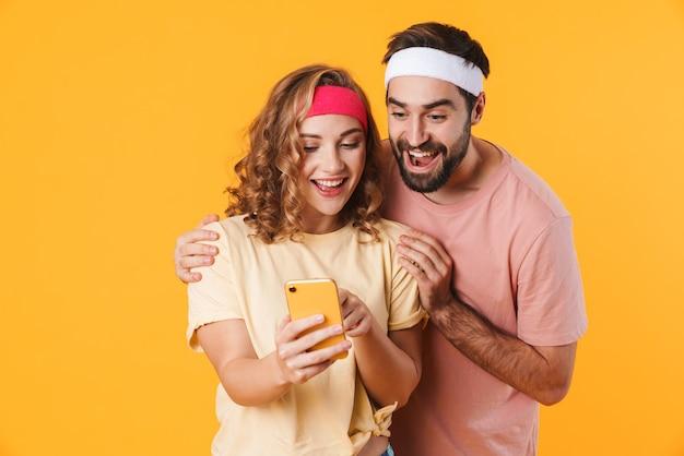 Retrato de um jovem casal feliz e esportivo usando faixas na cabeça, regozijando-se ao usar o celular isolado